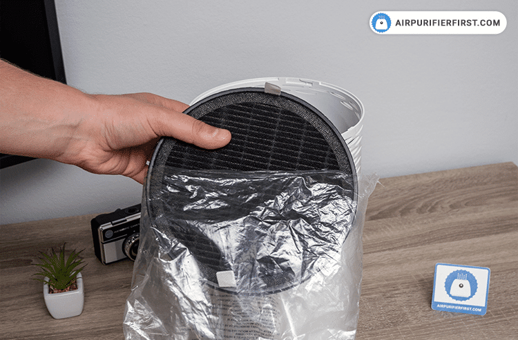 Removing plastic bag from a new filter.